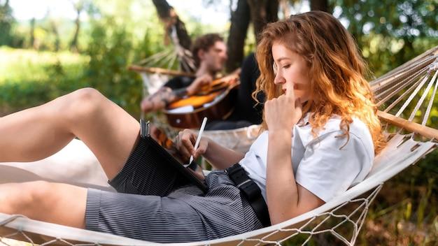 해먹에 누워 있는 커플 젊은 남자가 기타를 치고 있는 동안 여자는 스타일러스로 태블릿을 사용