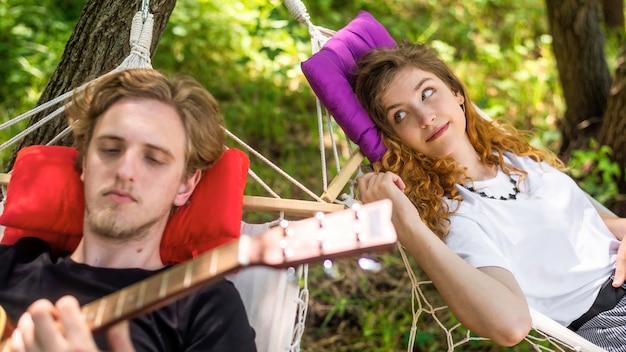 젊은 남자가 기타를 치는 동안 해먹에 누워 있는 커플