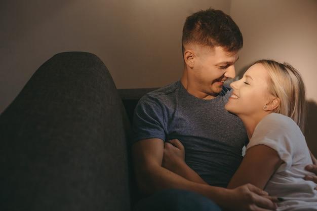 Пара, лежа на диване и улыбаясь друг другу