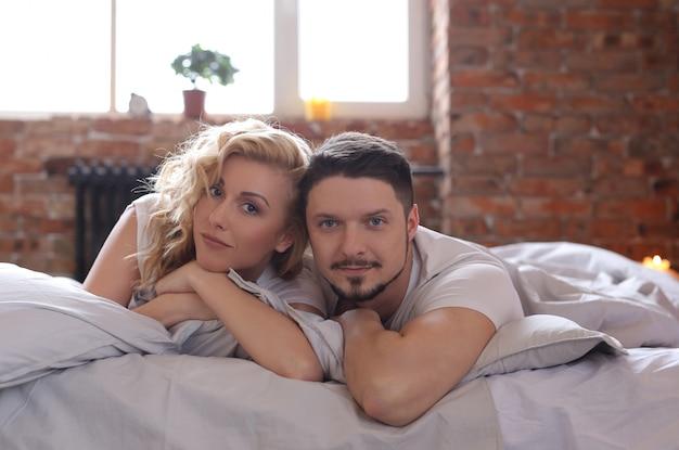 Пара лежит на кровати и смотрит в камеру