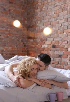 Пара лежит на кровати и занимается любовью