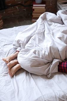 ツインパジャマ、足のビューでベッドに横になっているカップル