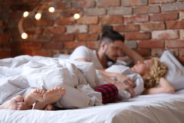 下着姿でベッドに横になっていると話すカップル