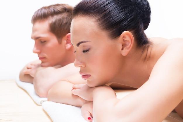 スパサロンのマッサージデスクに横たわっているカップル。美容トリートメントのコンセプト。