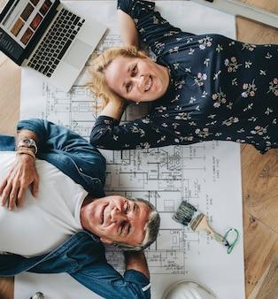 彼らの新しい家の木の床に横たわっているカップル