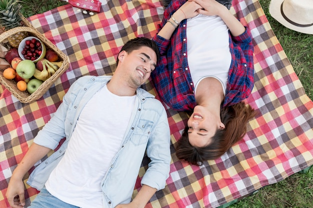 Couple lying on a picnic blanket top view