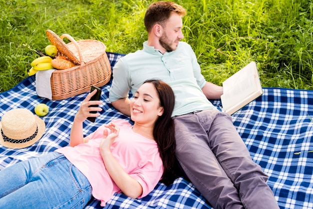 Couple lying on picnic plaid and relaxing