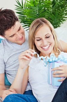 Couple lying on the sofa with a present