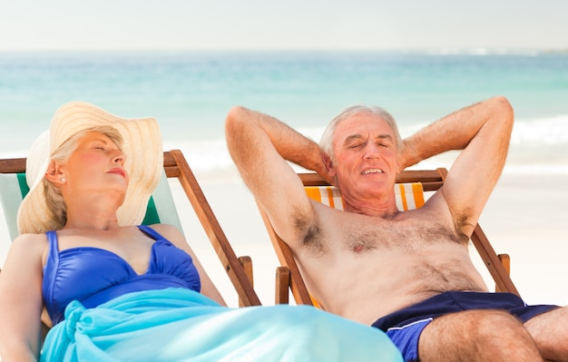 Couple lying in their deck chairs