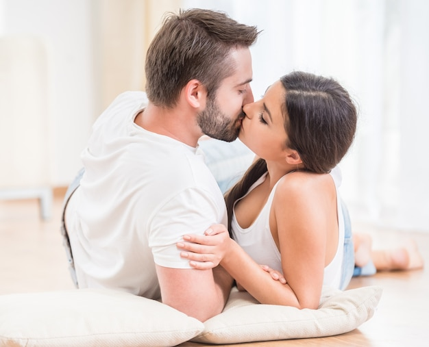 Couple lying together on the floor at home and kissing.