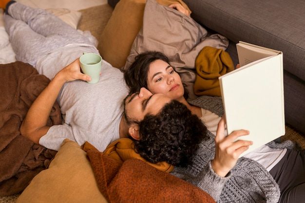 Couple lying together on the sofa while reading