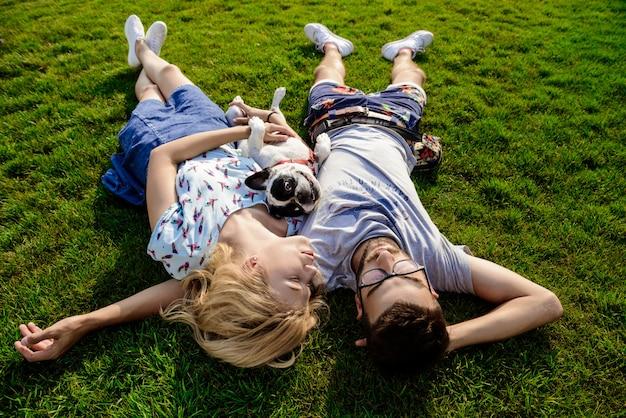 Coppia la menzogne con il bulldog francese su erba in parco