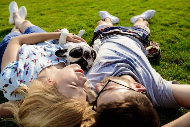 Пары лежа с французским бульдогом на траве в парке