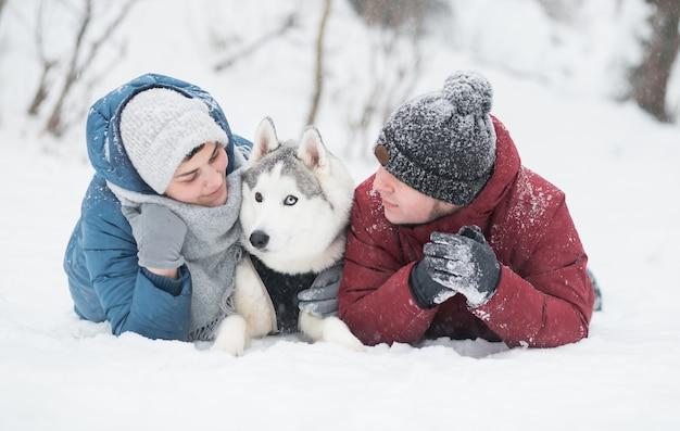 雪の冬にシベリアンハスキーと横たわっているカップル。滝。バレンタインデー。降雪。幸せな家族。犬。高品質の写真