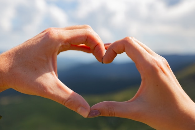 The couple make a heart with their hands on the background of the sky.