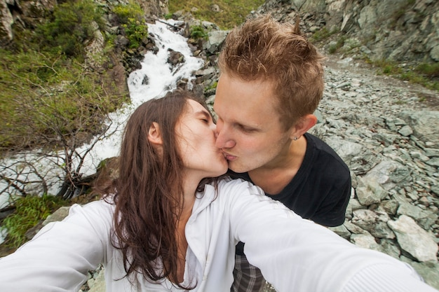 Couple makes a selfie against the background of a mountain  nature
