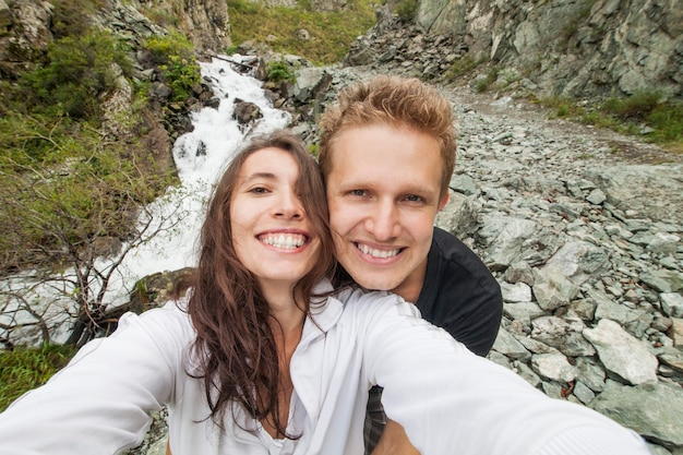 Couple makes a selfie against the background of a mountain stream and pure nature