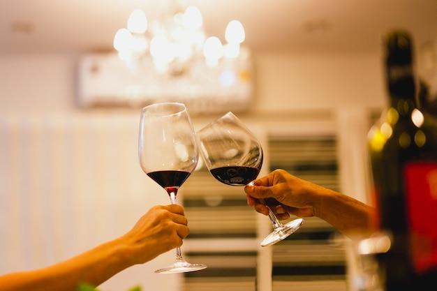 Пара делает тост с бокалами красного вина на званом обеде