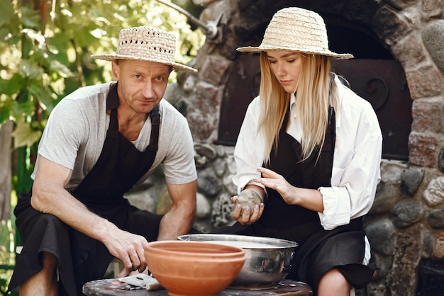 Пара делает вазу из глины