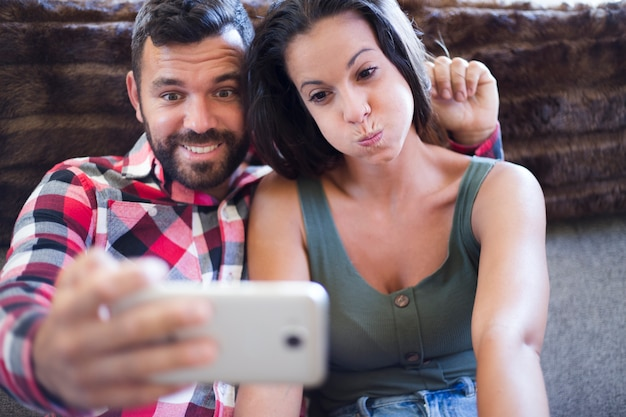Couple making funny expression while taking selfie on cellphone