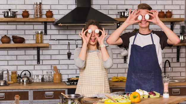 Couple making funny faces with eggs in kitchen