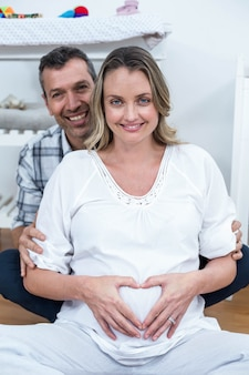 Couple making a heart shape on the pregnant belly with their hands