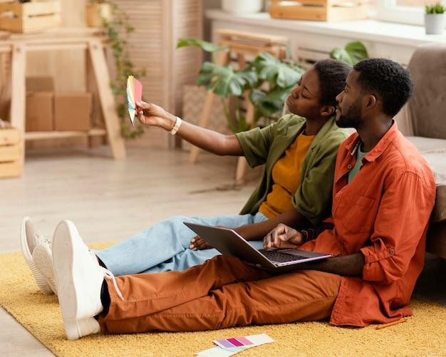 カラーパレットを使用して家を改築するための計画を立てるカップル