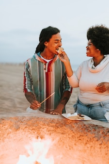 Couple making s'mores at the beach