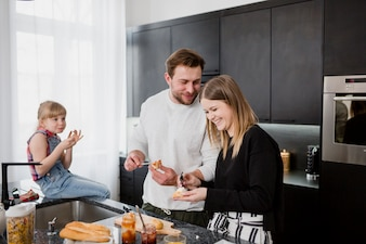 Couple making sandwiches near daughter