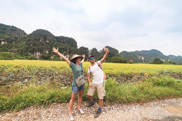 田んぼの中で田舎道でselfieを作るカップル