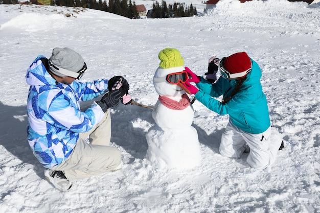 Пара делает снеговика на горнолыжном курорте. зимние каникулы