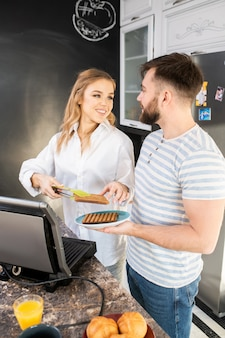 Couple making waffles in kitchen