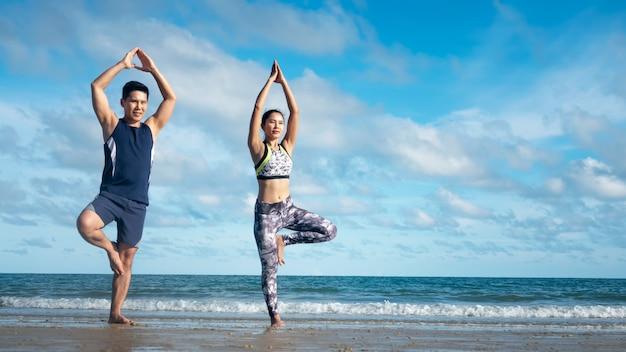 Couple making yoga exercises on beach.