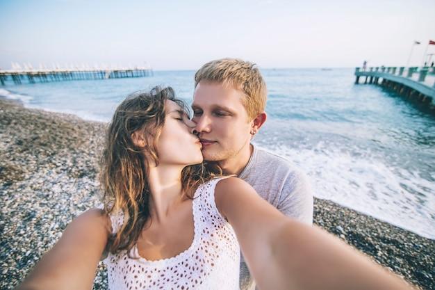 Пара мужчина и женщина делают селфи крупным планом на фоне моря и галечного пляжа