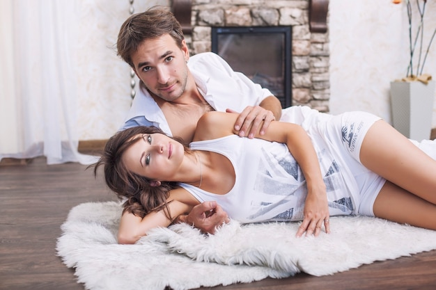 Пара мужчина и женщина обнимаются дома, лежа на ковре