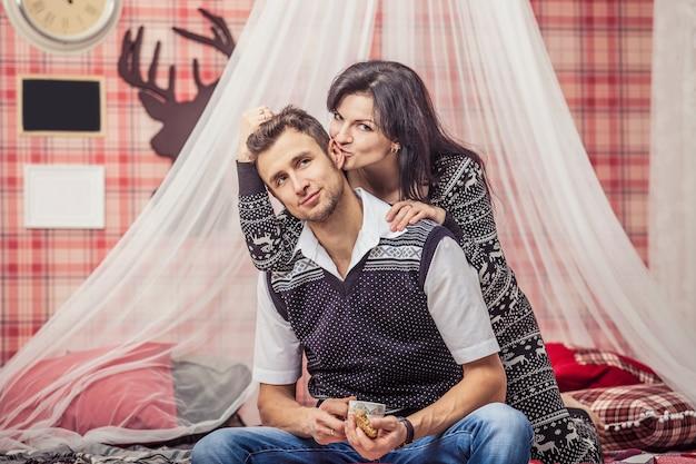 赤いクリスマスのインテリアでビスケットとお茶を飲む自宅の寝室でカップルの男性と女性