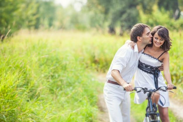 自然の中で自転車と幸せな結婚式のスタイルのカップルの男性と女性