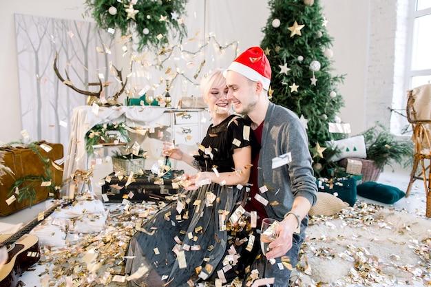 シャンパンを飲み、金色の紙吹雪で遊ぶ屋内でカップルの男性と女性