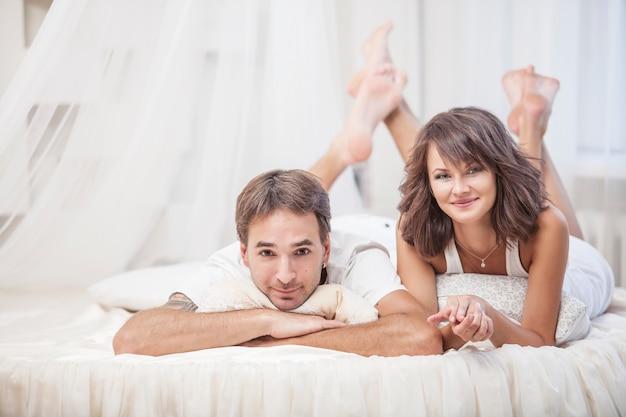 Пара мужчина и женщина лежали, обнимаясь на кровати дома. любовь в семейных отношениях
