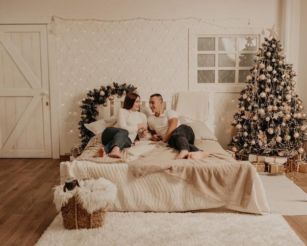 Пара мужчина и женщина лежат на кровати в спальне возле елки. украшенный дом на новый год