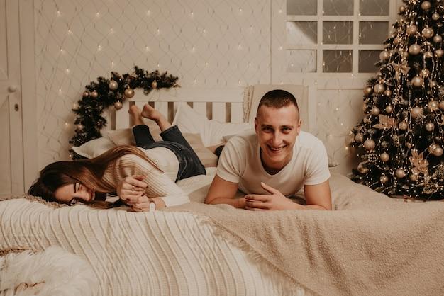 Пара мужчина и женщина лежат на кровати в спальне возле елки