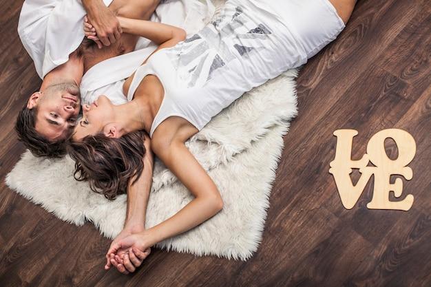 碑文の愛とマットの床に横たわっているカップルの男性と女性。家族、幸福、愛情、家