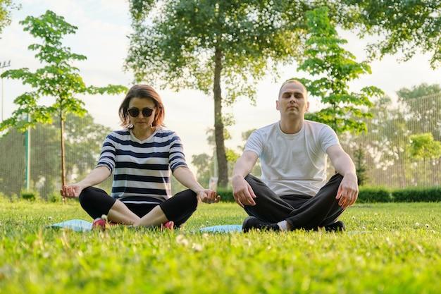 커플, 남자와 여자는 로터스 위치에 매트에 공원에 앉아 명상. 요가, 피트니스, 중년의 활동적인 건강한 라이프 스타일
