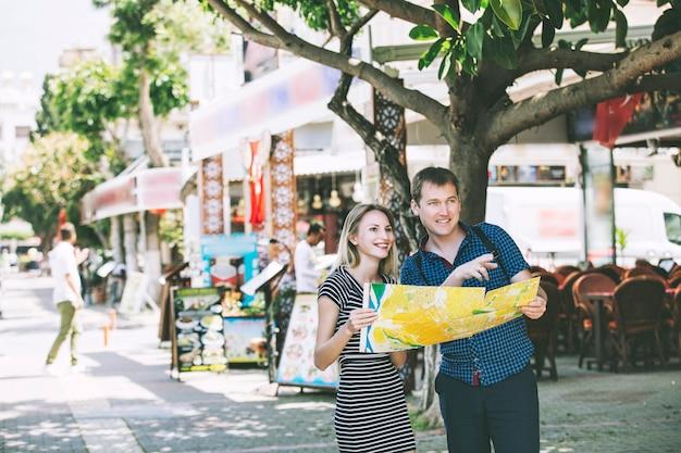 一緒にロマンチックで幸せな地図で街を歩いているカップルの男性と女性