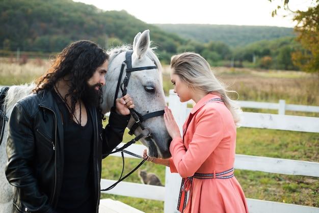 Пара мужчина и женщина, прогулки на ранчо с породистой лошадью. красивая девушка в розовом платье и парень, одетый как ковбой. люди счастливы и хорошо проводят время.