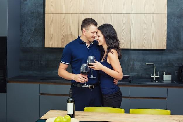 Пара мужчина и женщина молодые красивые и счастливые на кухне с бокалами winan