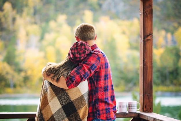 ホットドリンクのマグカップと自然の中で木造住宅のポーチで幸せな若いカップルの男性と女性