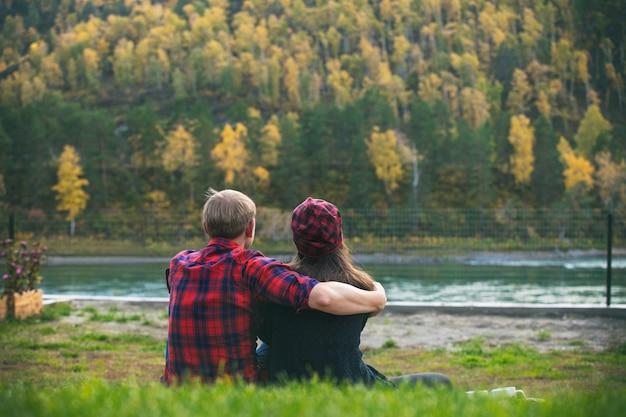 自然の中で草の上の毛布の上に座って若い美しい幸せなカップルの男性と女性