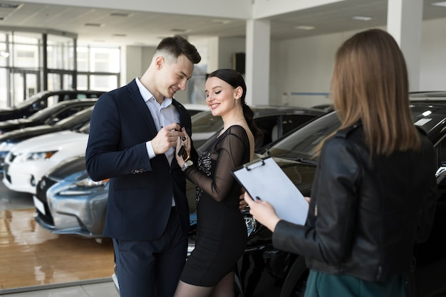 Couple of man and woman are happy to buy a new car in a car dealership with the seller