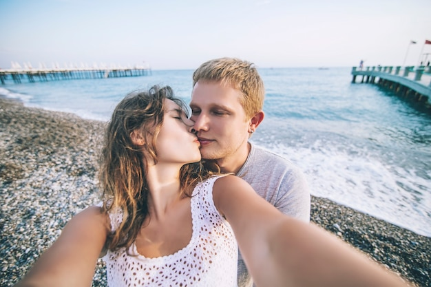 Couple man and woman doing a selfie closeup on background of the sea and a pebbly beach